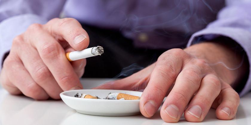 Hombre manteniendo un cigarro en un cenicero