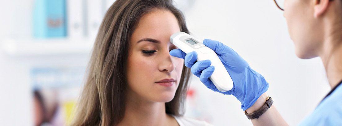¿Que se considera fiebre? médico tomando la temperatura con un termómetro a una paciente