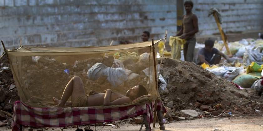 En India, un hombre con un mosquitero en su cama.